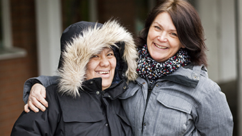 two smiling women in coats